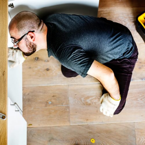 Man fixing kitchen sink - image by © rawpixel